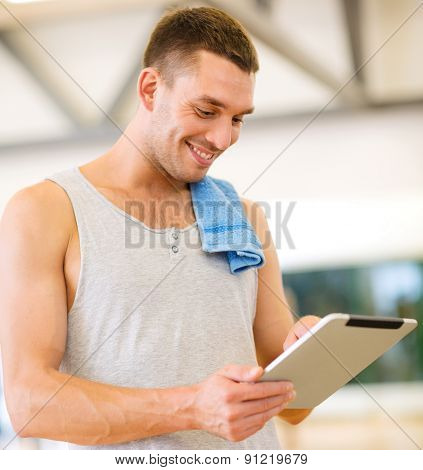 fitness, sport, training, gym, technology and lifestyle concept - young man with tablet pc computer and towel in gym