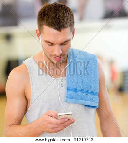 fitness, sport, training, gym, technology and lifestyle concept - young man with smartphone and towel in gym