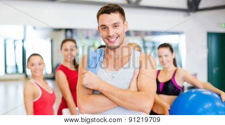 fitness, sport, training, gym and lifestyle concept - smiling man standing in front of the group of people in gym