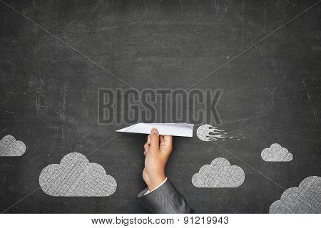 Black blank blackboard with hand holding paper plane