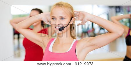 fitness, sport, training, gym and lifestyle concept - group of smiling people with trainer exercising in the gym