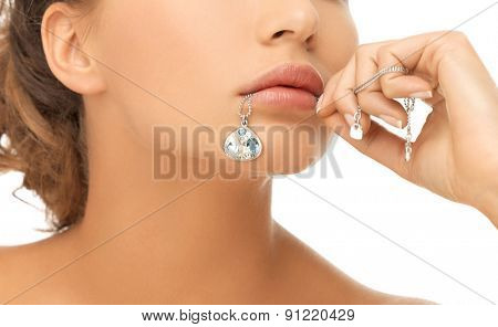 bride and wedding concept - beautiful woman holding shiny diamond pendant in mouth
