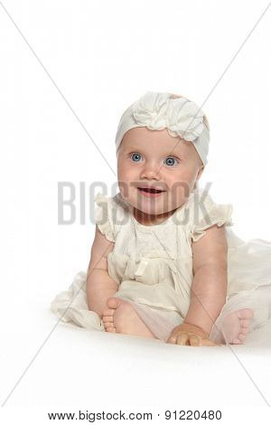 baby girl child sitting down on white blanket smiling happy pink fashion portrait face studio shot isolated on white caucasian