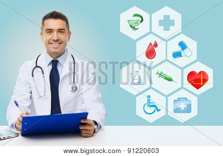 medicine, profession, technology and people concept - happy male doctor with clipboard and stethoscope over blue background with medical icons
