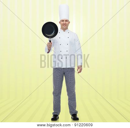 cooking, profession and people concept - happy male chef cook holding frying pan over yellow background