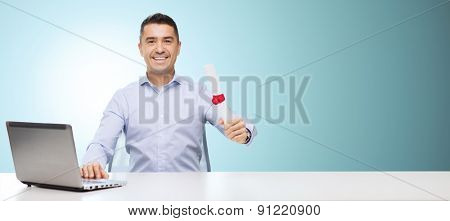 education, graduation, business, technology and people concept - smiling man with diploma and laptop computer sitting at table over blue background