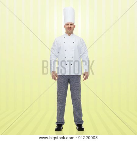 cooking, profession and people concept - happy male chef cook over yellow background