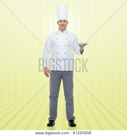 cooking, profession, advertisement and people concept - happy male chef cook showing something on empty plate over yellow background