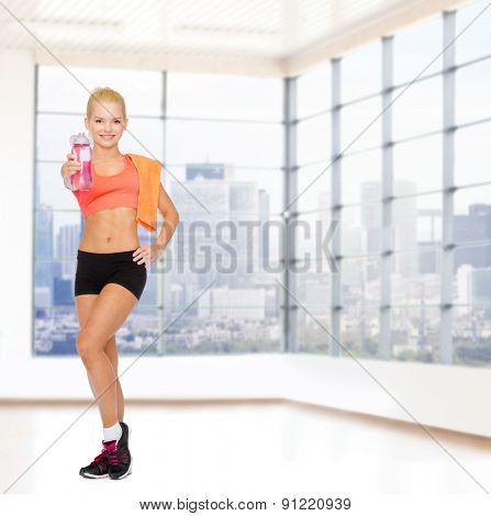 sport, fitness, healthy lifestyle and people concept - sporty woman with orange towel and bottle of water over gym background