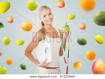 healthy eating, diet, weight control and people concept - happy young woman with scale, green apple and measuring tape over gray background with falling fruits