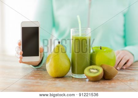 healthy eating, technology, diet and people concept - close up of woman hands with smartphone, fruits and fresh juice sitting at table