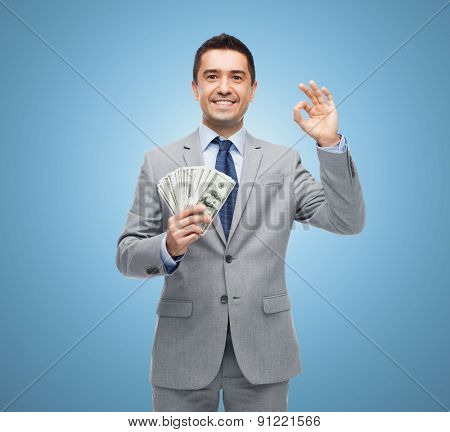 business, people and finances concept - smiling businessman with american dollar money over blue background