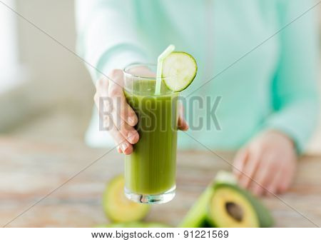 healthy eating, food, dieting and people concept - close up of woman hands with green fresh juice and vegetables sitting at table