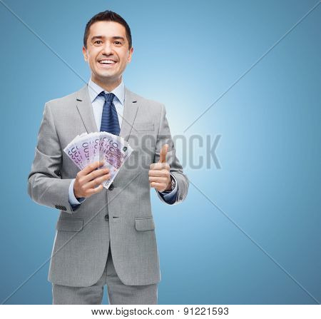 business, people and finances concept - smiling businessman with european money showing thumbs up over blue background