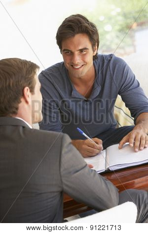 Man Meeting With Financial Advisor At Home