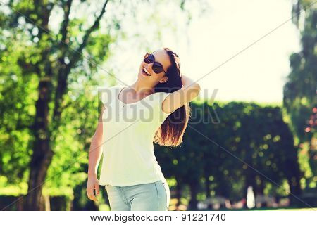 summer, leisure, vacation and people concept - smiling young woman wearing sunglasses standing in park