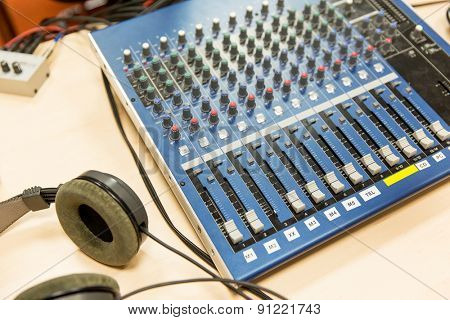 technology, electronics and equipment concept - control panel and headphones at recording studio or radio station