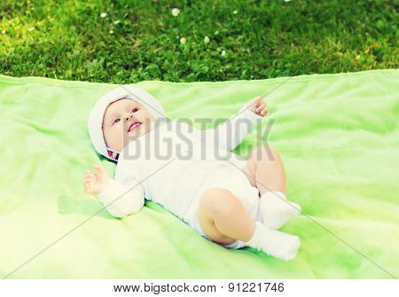 child, childhood and toddler concept - smiling baby lying on blanket and looking up
