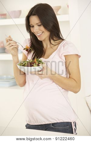 Pregnant Woman Eating Salad In Kitchen At Home