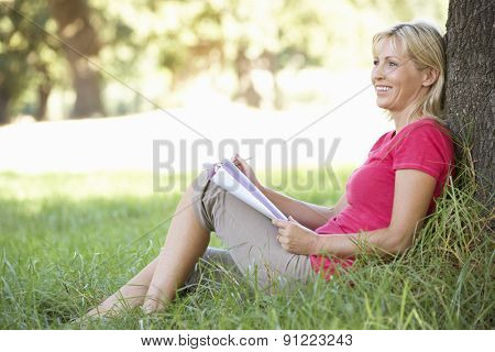 Middle Aged Woman Sketching In Countryside Leaning Against Tree