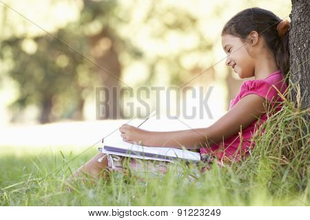 Young Girl Sketching In Countryside Leaning Against Tree