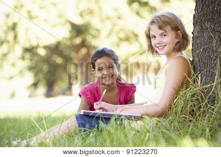 Two Young Girls Sketching In Countryside Leaning Against Tree