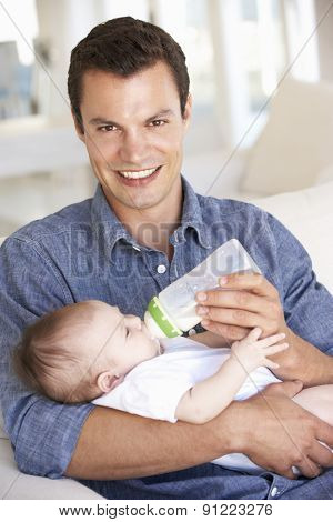 Young Father With Baby Feeding On Sofa At Home