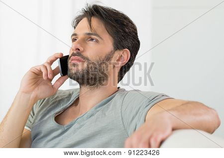 Portrait of thoughtful man talking on cellphone at phone