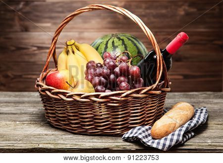 Basket full of fresh fruit, wooden background
