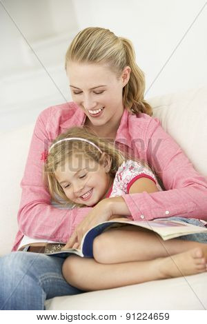 Mother And Daughter Reading Book In Bedroom