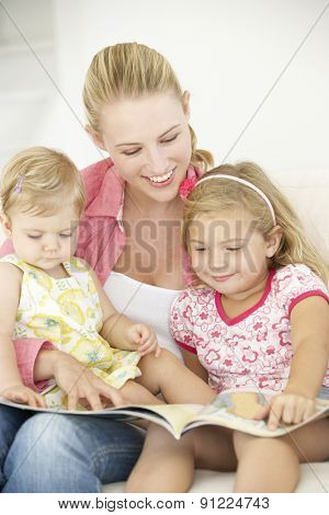 Mother And Daughters Reading Book At Home