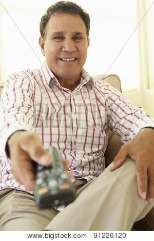 Senior Hispanic Man Using TV Remote Control