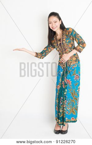 Full length portrait of Southeast Asian girl in batik dress hand holding something standing on plain background.
