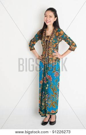 Full length Southeast Asian woman in batik dress standing on plain background.