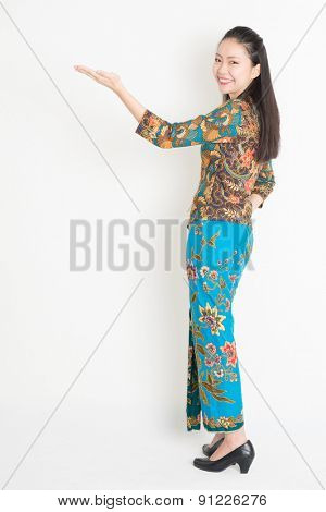 Full length portrait of Southeast Asian female in batik dress hand holding something standing on plain background.