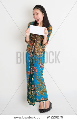 Full length portrait of excited Southeast Asian female in batik dress hands holding an envelope standing on plain background.