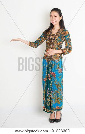 Full length portrait of Southeast Asian woman in batik dress hand holding something standing on plain background.