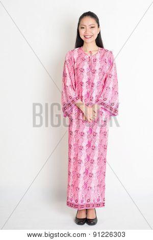 Full body portrait of happy Southeast Asian girl in pink batik dress standing on plain background.