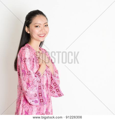 Portrait of happy Southeast Asian girl in pink batik dress standing on plain background.