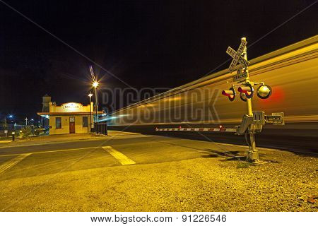 train passes the railroad crossing in the night