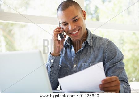 Young Man On Phone Using Laptop At Home