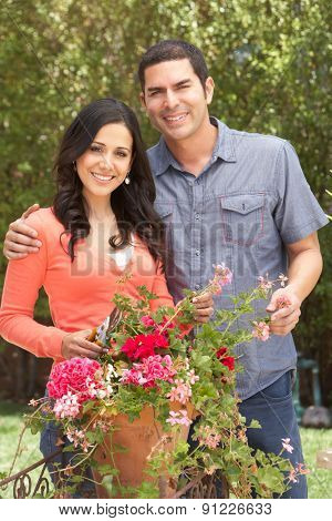 Hispanic Couple Working In Garden Tidying Pots