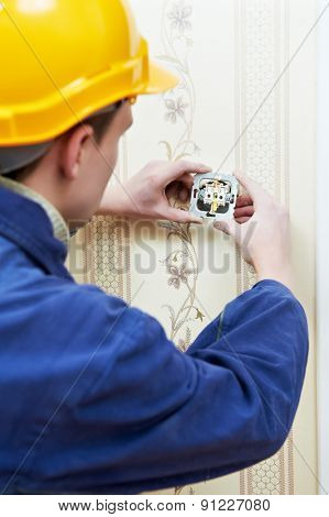 electrician worker installing and light switch or power wall outlet socket