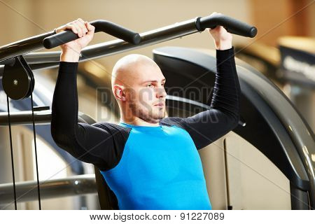 Fitness: bodybuilder man doing exercises with weight training equipment on sport gym club