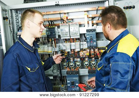 two electricians builder engineers discussing electrical components equipment near fuseboard distribution box