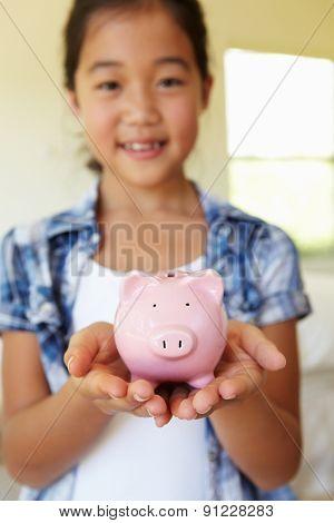 Young girl holding piggybank