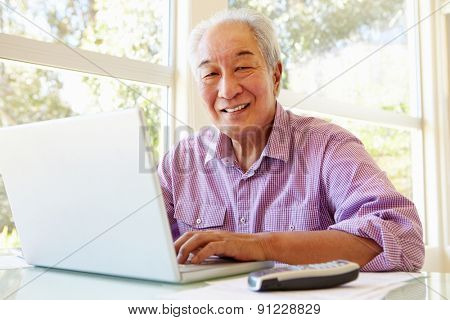 Senior Taiwanese man working on laptop