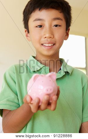 Young boy holding piggybank