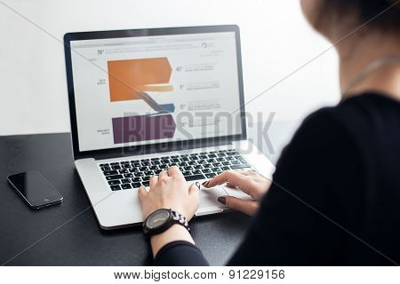 Shot of a young lady working with laptop, woman's hands on notebook computer and smart phone, buisin