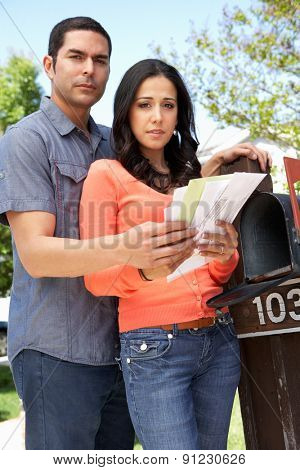 Worried Hispanic Couple Checking Mailbox